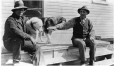 MP-0000.597.147 | Two men seated on wood steps with two dogs, 1910-27 | Photograph | Captain George E. Mack |  |