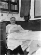 MP-0000.597.177 | Man holding a book, reclining on couch made up as a bed, 1917-27 | Photograph | Captain George E. Mack |  |