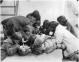 MP-0000.597.205 | Inuit group eating from pots with large spoons, 1910-27 | Photograph | Captain George E. Mack |  |