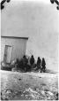 MP-0000.597.429 | Inuit group with furs outside wooden building, 1910-27 | Photograph | Captain George E. Mack |  |