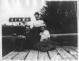 MP-1975.26.49 | Three unidentified people seated on wharf, Hotel Malhiot, Shawinigan, QC, about 1900, copied ca.1975 | Photograph | Anonyme - Anonymous |  |