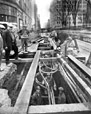 BELL-6124 | Telephone crew places cable underground at the corner of Ste-Catherine Street and Union Avenue, Montreal, QC, 1930 | Photograph | Millar Studio |  |
