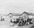 19760213005   Group of Blackfoot sit near the Royal North West Mounted Police barracks in Fort Macleod, 1894   Photograph        